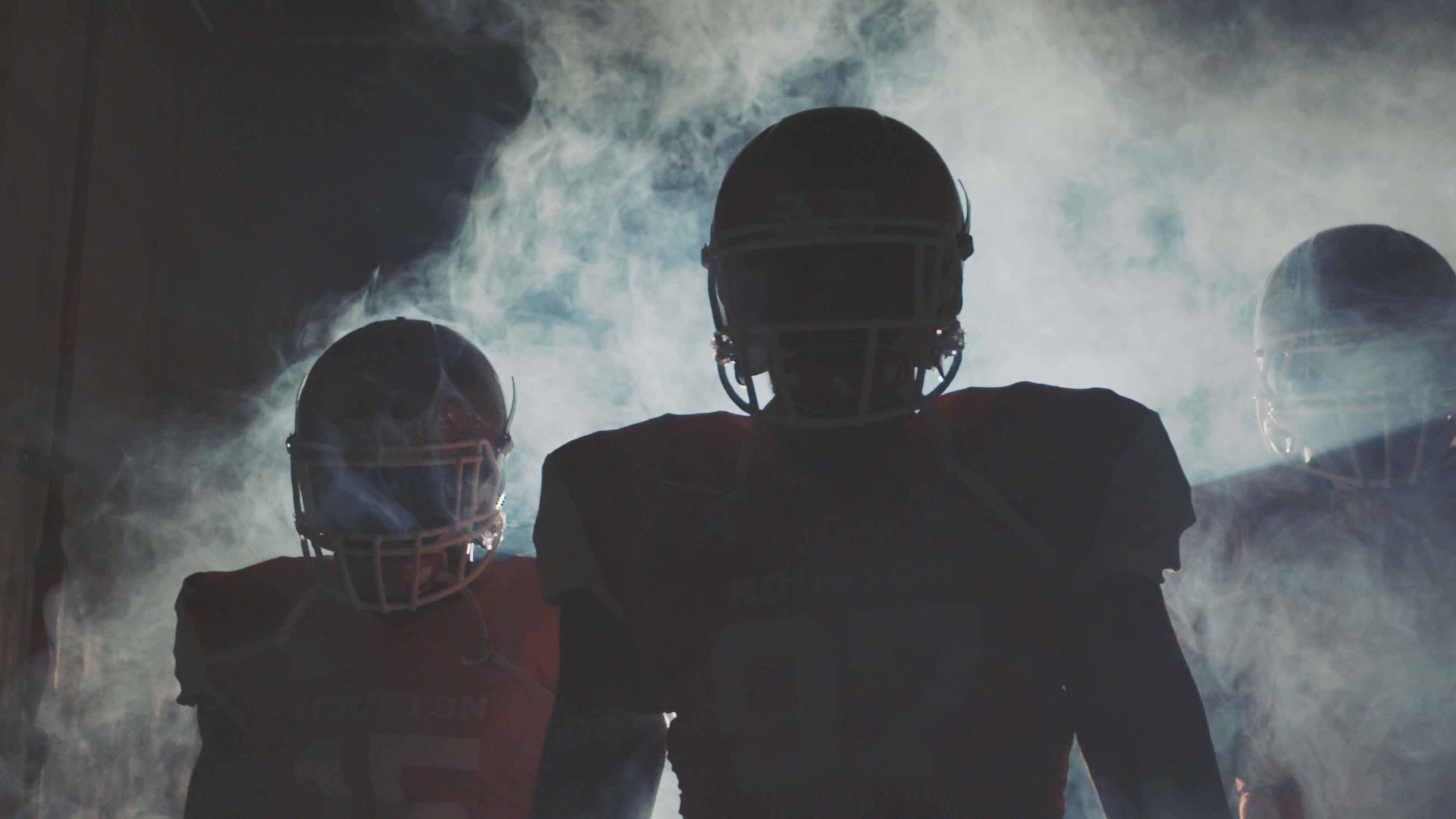 Football Players in Tunnel with Dramatic Lighting and Smoke